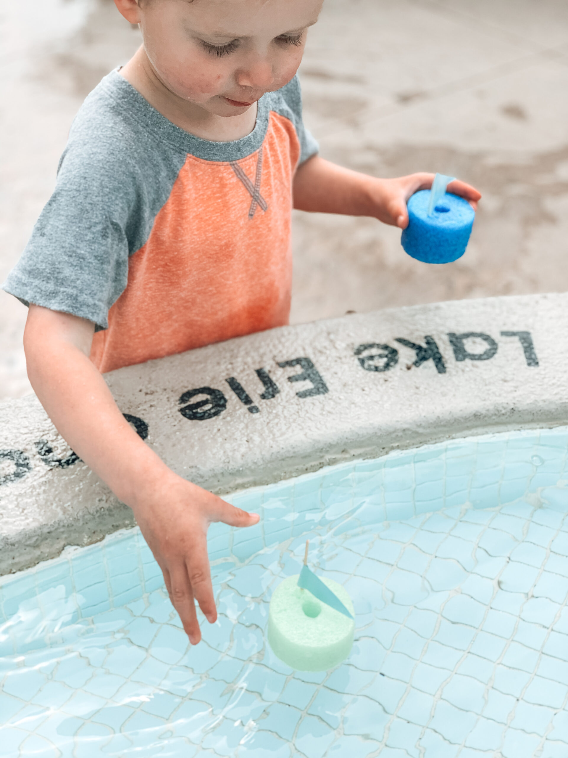Kids playing with DIY toy boats made of pool noodles