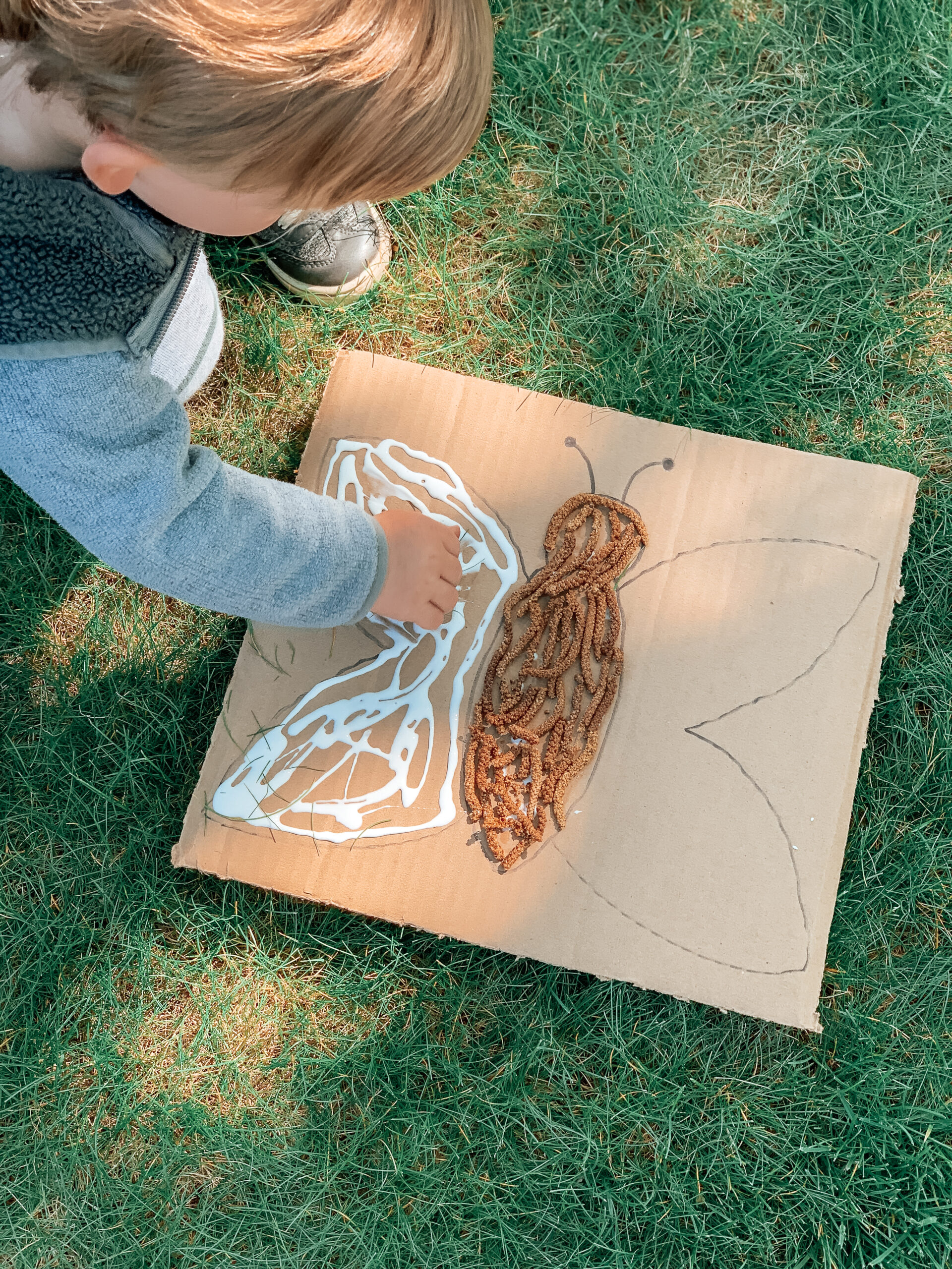 child making art with nature and repurposed cardboard